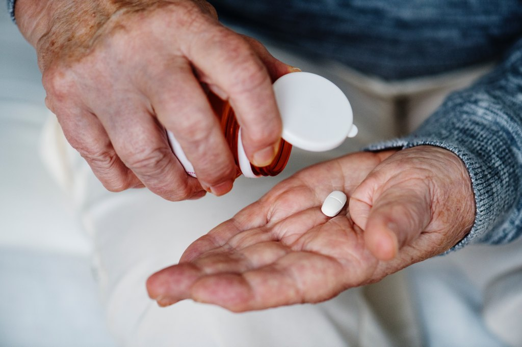 Man pouring out one pill from bottle